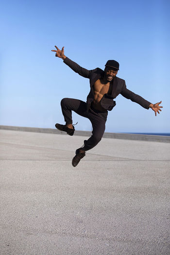 Front view young black man wearing casual clothes jumping in urban background. Lifestyle concept. Millennial african guy wearing sunglasses outdoor Mid-air Sky Full Length Lifestyles Real People Leisure Activity Jumping One Person Day Nature Human Arm Casual Clothing Clear Sky Arms Outstretched Men Limb Motion Enjoyment Blue Outdoors Teenager African American Black Man Dancing Muscular Build Suit Daylight Blue Sky Copy Space Males  Man Young Adult Bearded Elegant Attractive Wellbeing