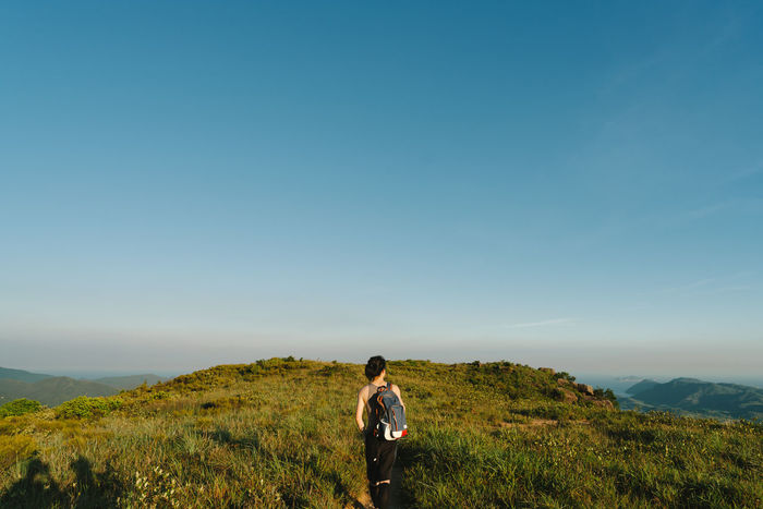 Walking Adult Adults Only Beauty In Nature Clear Sky Copy Space Day Full Length Grass Hiking Landscape Nature One Man Only One Person Only Men Outdoors People Sky Standing Sunset Young Adult