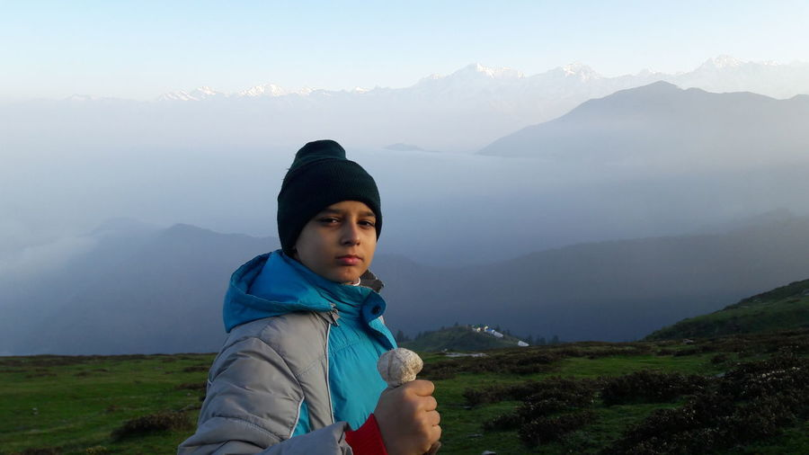 Portrait of teenage boy standing on himalayas during foggy morning