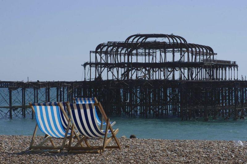 Chairs Against Brighton Pier At Beach
