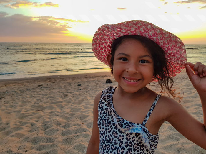 Close-up portrait of girl smiling while wearing hat at beach