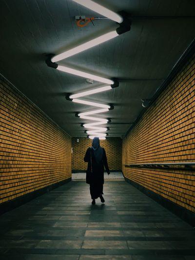 Rear view of woman walking in illuminated subway