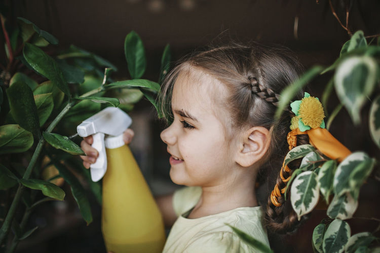 Close-up of girl looking at flowering plants