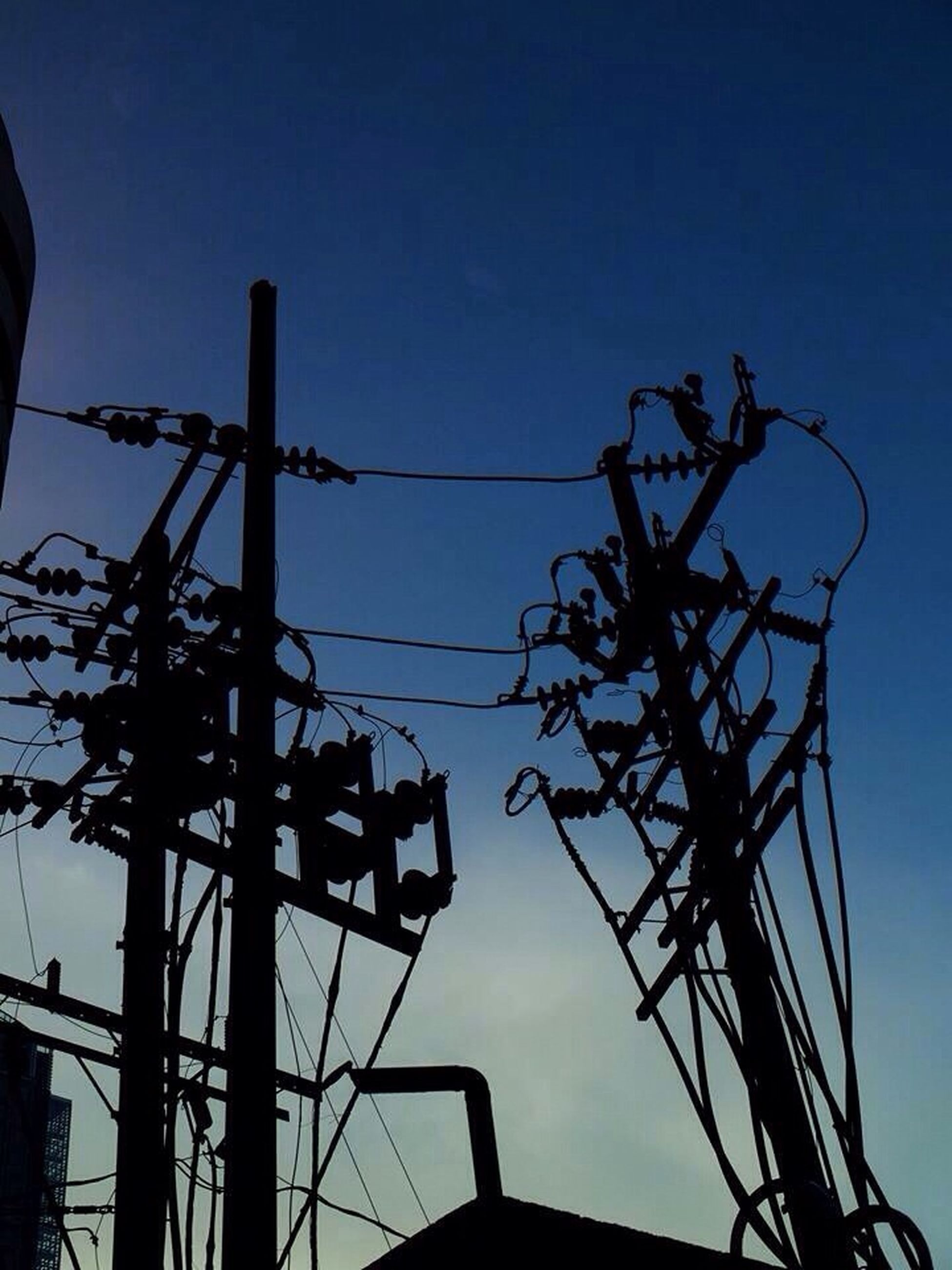 low angle view, silhouette, sky, power line, electricity, electricity pylon, built structure, clear sky, technology, power supply, blue, fuel and power generation, connection, architecture, street light, cable, dusk, building exterior, outdoors, lighting equipment