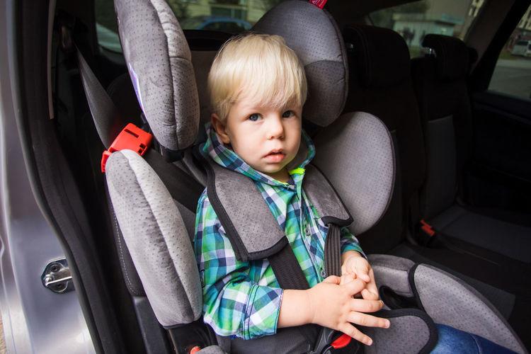Cute boy sitting in car