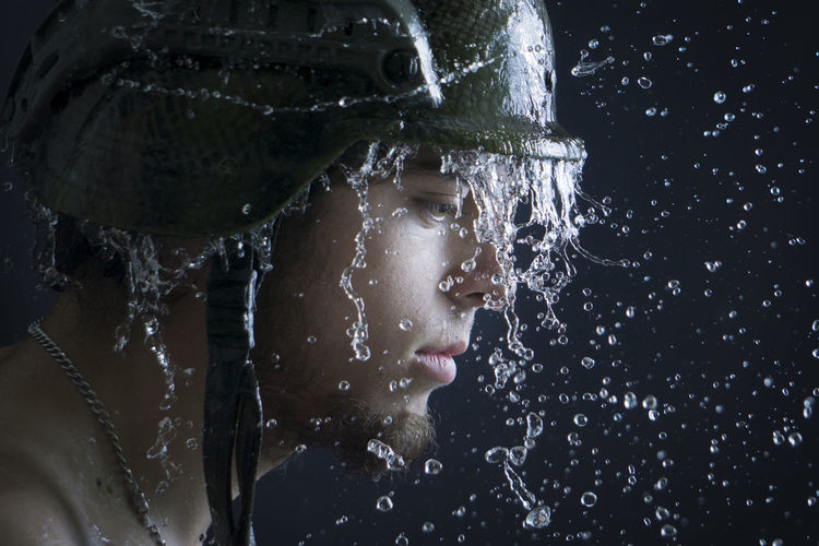 Close-Up Of Wet Young Man Over Black Background
