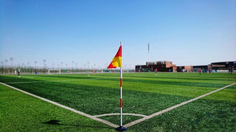 Flag on soccer field against clear sky