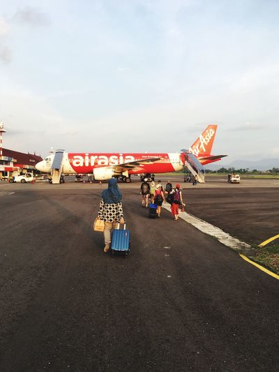 A woman with luggage walking towards airplane Sky Transportation Rear View Real People Outdoors Day Land Vehicle Road Large Group Of People People Woman Airport Airport Runway Travelling Holiday Air Asia Traveller Flying