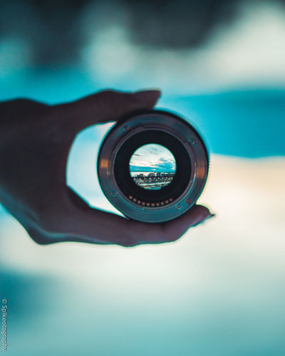Hand Human Hand Human Body Part One Person Holding Photography Themes Camera - Photographic Equipment Lens - Optical Instrument Unrecognizable Person Real People Photographic Equipment Technology Circle Close-up Geometric Shape Body Part Focus On Foreground Human Finger Finger Digital Camera SLR Camera