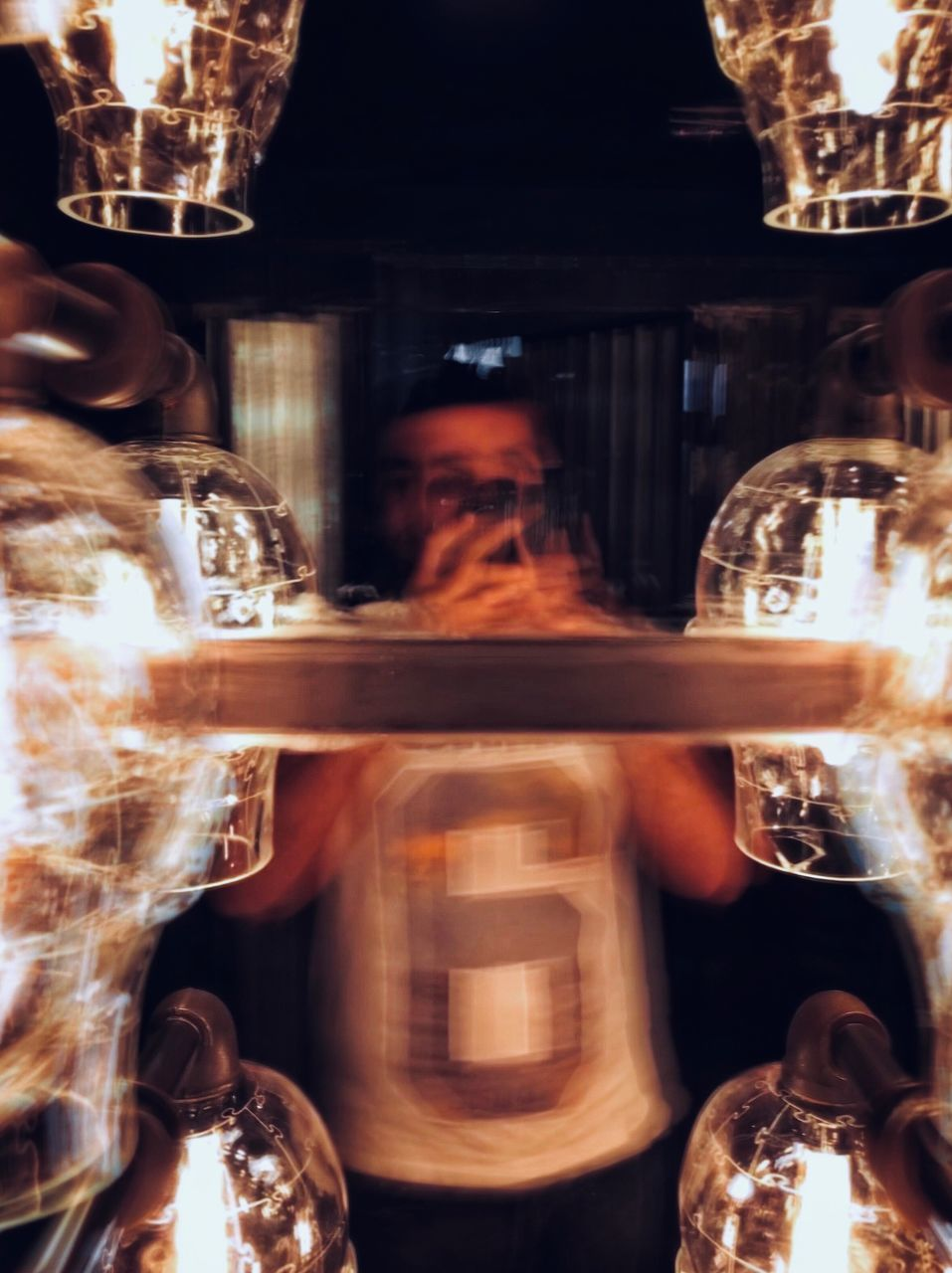 REFLECTION OF MAN IN GLASS OF ILLUMINATED MIRROR