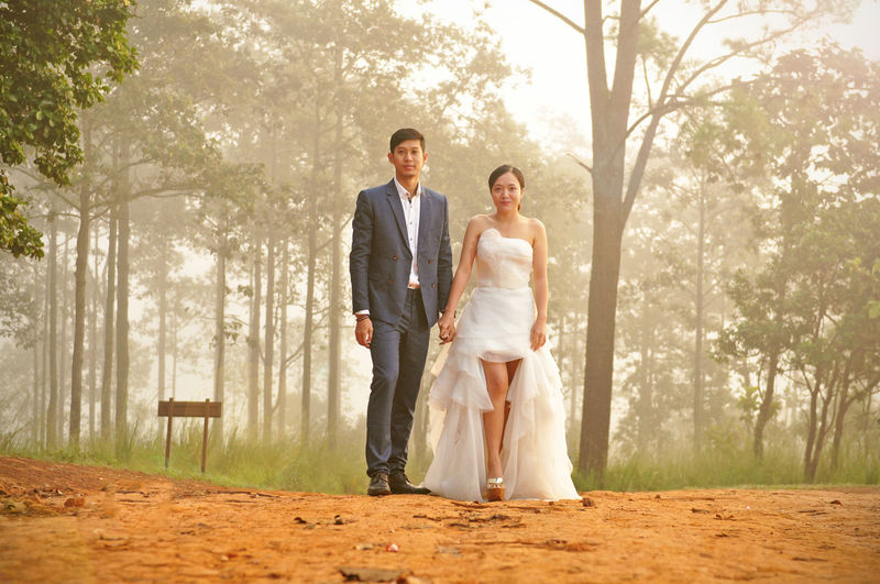 Full length of couple standing against trees