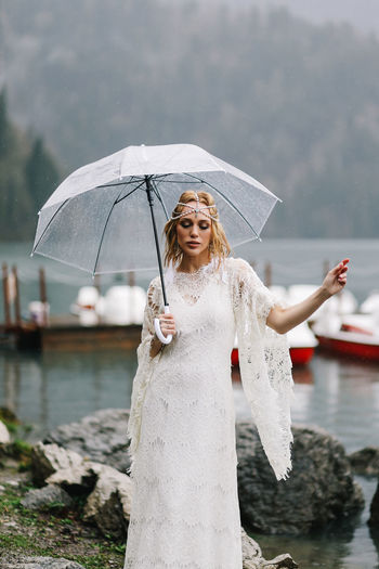 A young woman in a white lace wedding dress stands in the rain among the sea and mountains