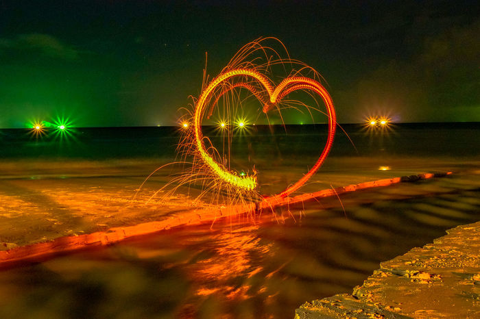 heart image from steel wool on the beach Night Motion Illuminated Long Exposure Wire Wool Blurred Motion Glowing Spinning Circle Nature Speed Geometric Shape Outdoors Light Trail Sparks Steel Wool, Fire Work, Heart Shape Smile Angray Water Sky No People Reflection Light Painting Lake Light