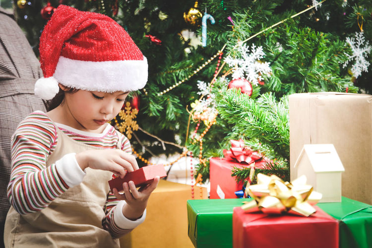Girl wearing santa hat sitting with gifts against christmas tree