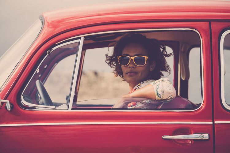 Serious lady on a old retro nice red car looking at you with open window glass - traveler with hippy freedom lifestyle and alternative vehicles One Woman Only Females Enjoying Life Freedom Red Car Vintage Casual Clothing Caucasian Mode Of Transportation Real People Transportation Glasses One Person Car Land Vehicle Headshot Lifestyles Portrait Motor Vehicle Leisure Activity Sunglasses Sitting Day Fashion Smiling Window Red Mature Adult Outdoors Car Door Young Woman 40-44 Years Fashion People
