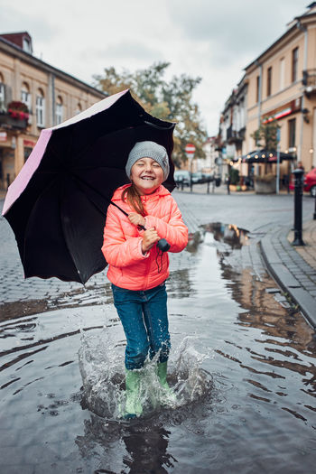 Happy smiling girl holding big umbrella jumping in the puddle during walk in a downtown on rainy day