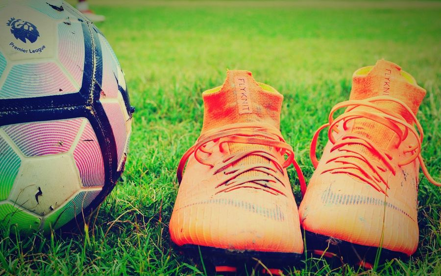 football boots on ground and a ball EyeEm Selects Low Section Human Leg Soccer Shoe Shoe Sport Relaxation Sock Grass Close-up Pair Grass Area Menswear Shoelace Soccer Field Stitching