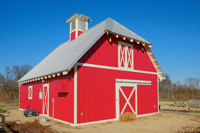 Red barn against a blue sky. Architecture Barn Blue Building Built Structure Countryside Day Exterior Landscape No People Outdoors Red Rural Sky Sunny Utility