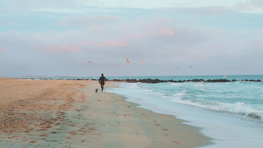 Silhouette Man Running On Beach Against Sky