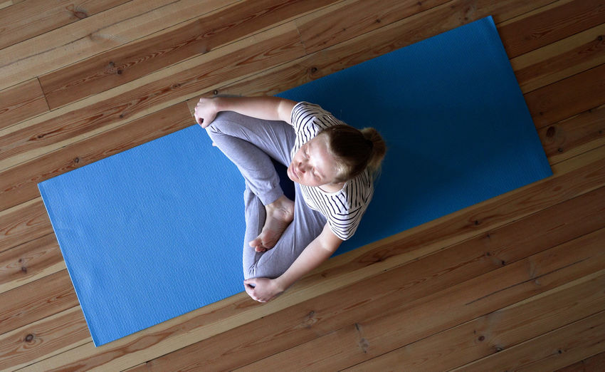 High angle view of girl on hardwood floor at home