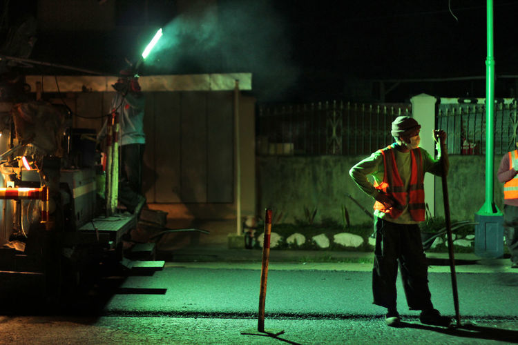 Full length of man working in factory at night