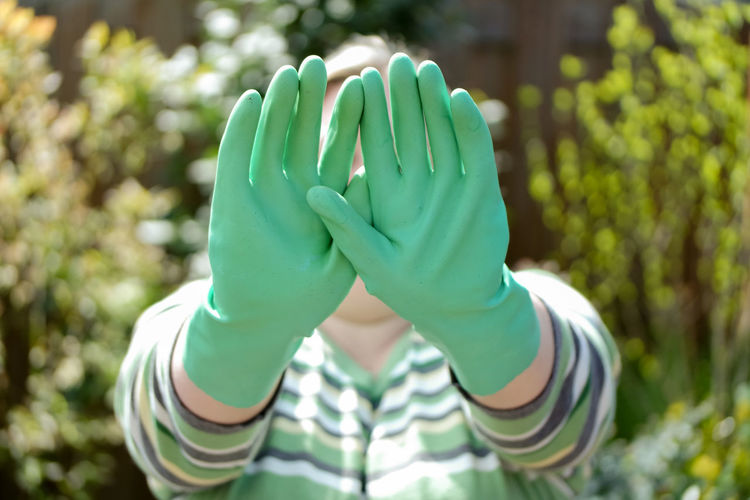 Close-up of woman wearing green gloves while standing against trees at yard