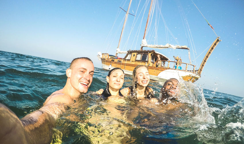Young millennial friends taking selfie and swimming at sailing boat sea trip - Rich guys and girls having fun in summer party day - Exclusive vacation concept - Tilted horizon on bright warm filter Luxury Friends Summer Young People Millenials Millennials Vacation Travel Fun Happy Sailing Boat Party Trip Sailboat Yacht Moment Ibiza Sail Caribbean Selfie Beach Group Adventure