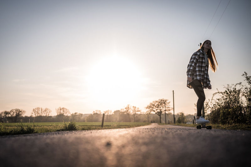 Rear view of man standing by road against sky during sunset