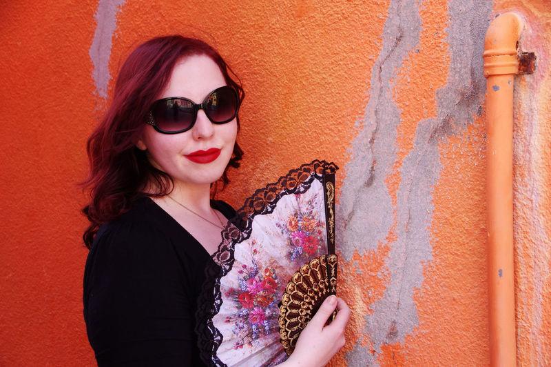 Portrait Of Woman With Folding Fan By Orange Wall