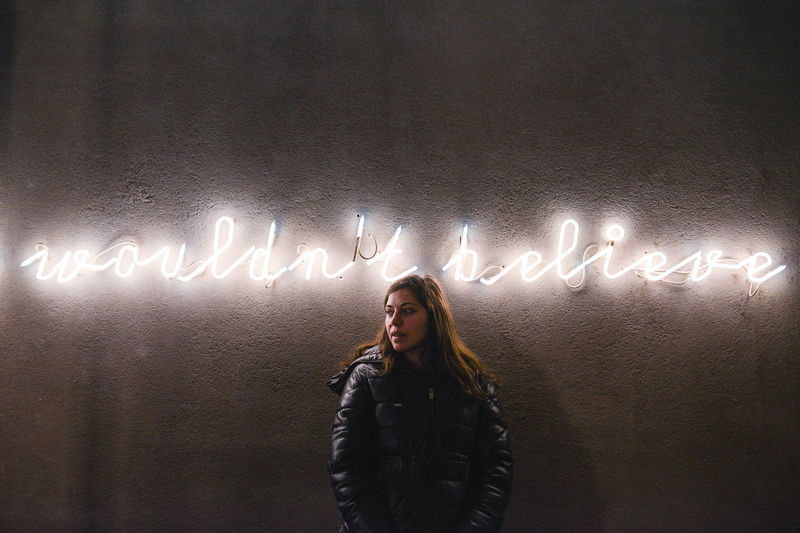 Woman looking away standing by illuminated text on wall