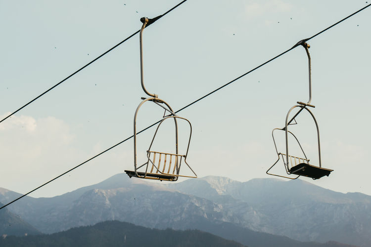 Low Angle View Of Ski Lift By Mountains Against Sky