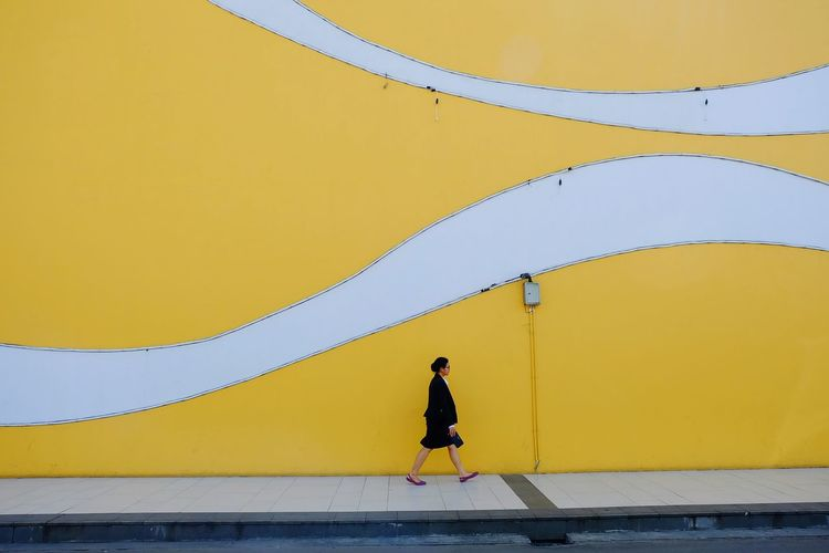 Side view of man walking against yellow wall