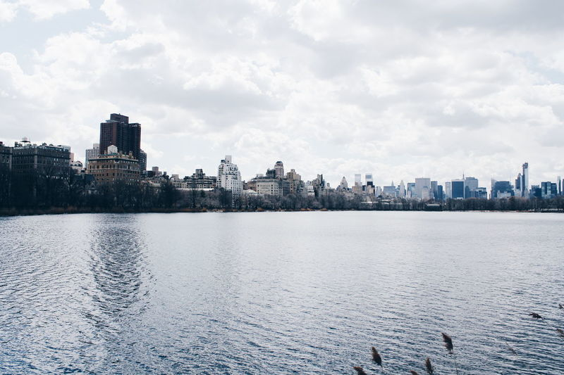 Architecture Building Exterior Built Structure Cityscape Development Distant Famous Place Human Settlement Lake Mid Distance Outdoors Reflection Residential District Sky Standing Water Town Tree Water Waterfront Central Park New York Manhattan Reservoir Skyline City
