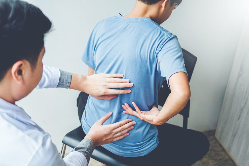 Rear View Of Doctor Examining Patient Sitting On Chair At Clinic