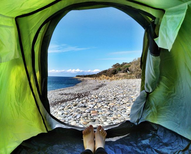 Low Section Of Person In Tent On Beach Against Sky