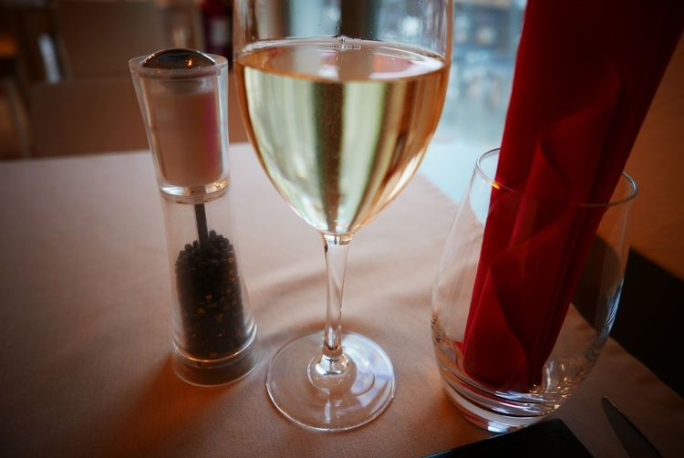 Close-up of white wine and pepper shaker on table in restaurant