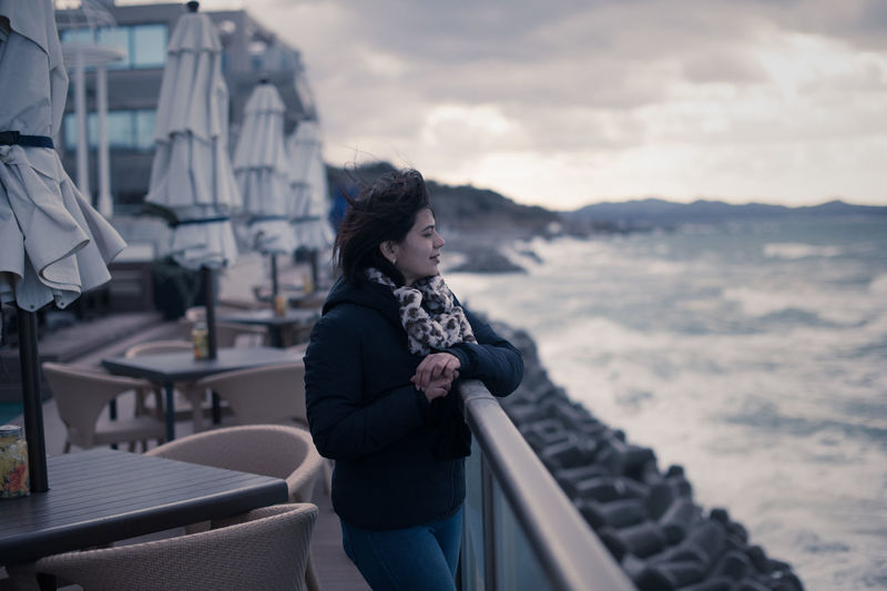 Woman standing by railing and sea against sky