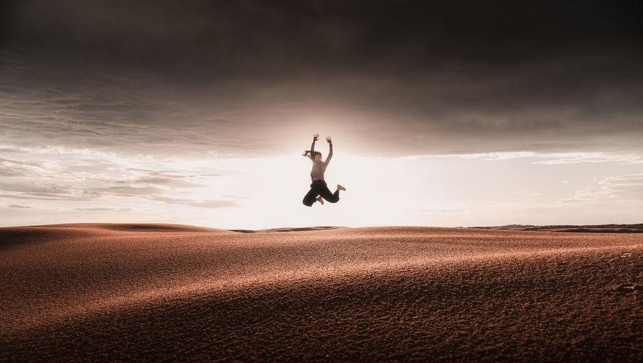 Women jumping on sand dunes against sky