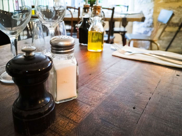 Close-up of salt and pepper shakers on table in restaurant