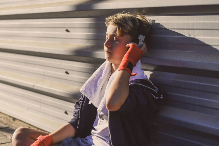 Boy listening to music through headphones while sitting against wall