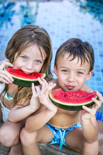 Cute Siblings Having Watermelon Against Swimming Pool