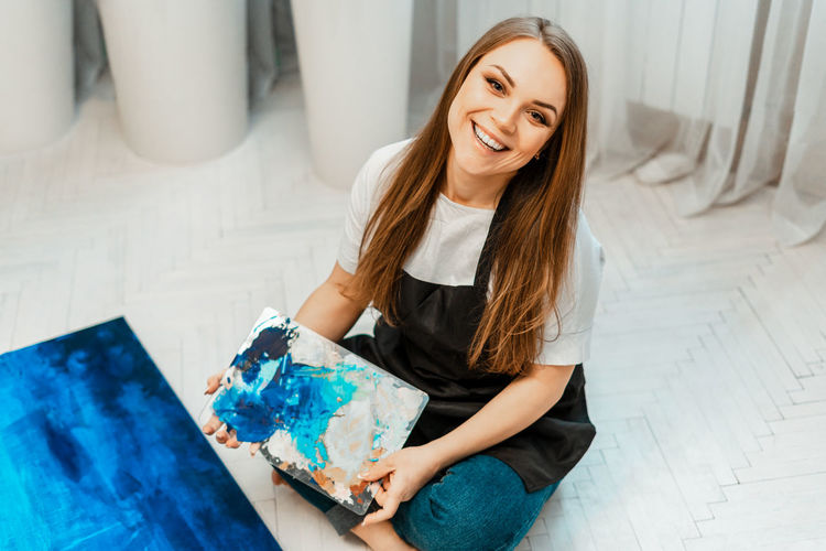 Portrait of smiling woman holding palette while sitting at home