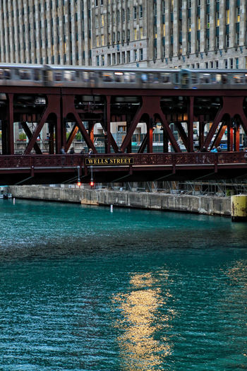 El train traveling across an elevated track over the Chicago River in the downtown loop and reflections of surrounding cityscape on the water. CTA Chicago Chicago River Chicago El Cityscape Downtown Chicago Elevated Track Reflection Transit Transportation Wabash Avenue Architecture Bridge - Man Made Structure Building Exterior Built Structure Day Drawbridge  El Train Glimmering Water Outdoors Reflections River Transportation Water Waterfront