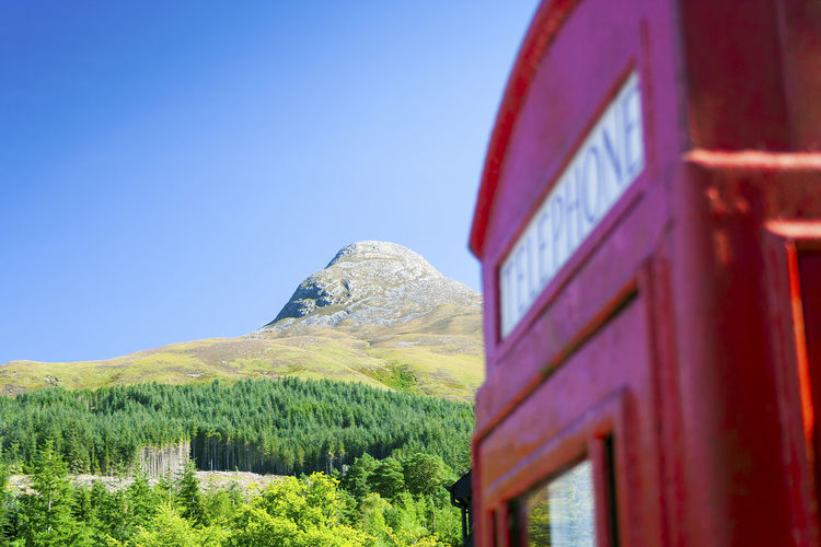 The Pap of Glencoe mountain in the Scottish Highlands named Sgurr na Cìche in Scottish gaelic with a juxtaposition out of focus telephone box Glencoe Green Juxtaposition Nature Red Scotland Sgurr Na Ciche Telephone Box The Pap Tree Blue Blue Sky Clear Sky Contrasting Highlands Landmark Landscape Mountain No People Outdoors