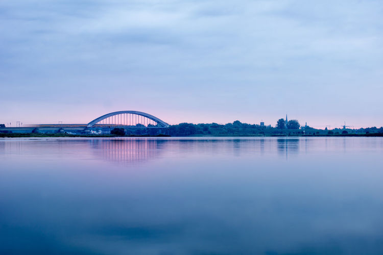 Long exposure of a view on culemborg the netherlands railway bridge train crossing blue pink sunrise