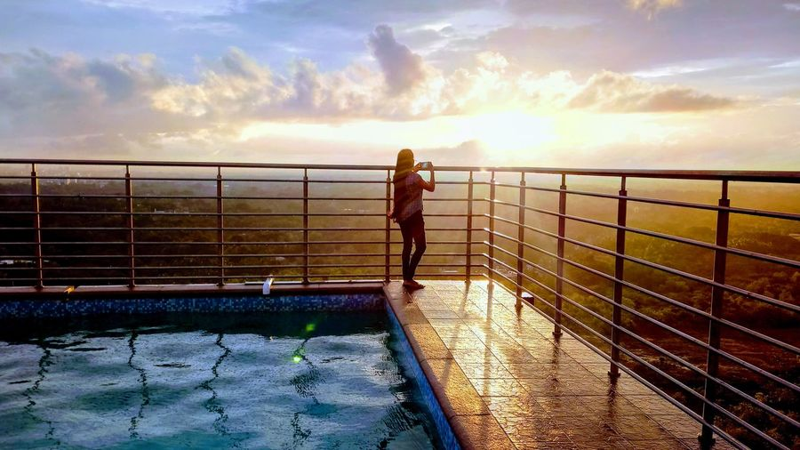 Woman standing by swimming pool against sky during sunset