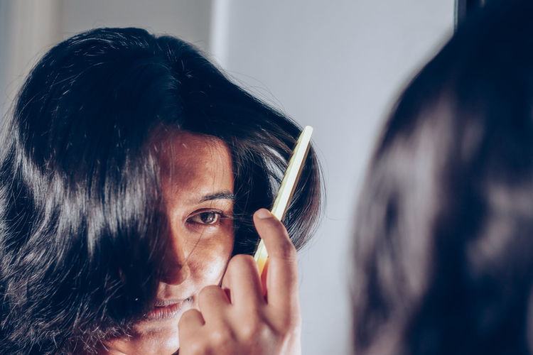 Reflection of woman combing hair on mirror