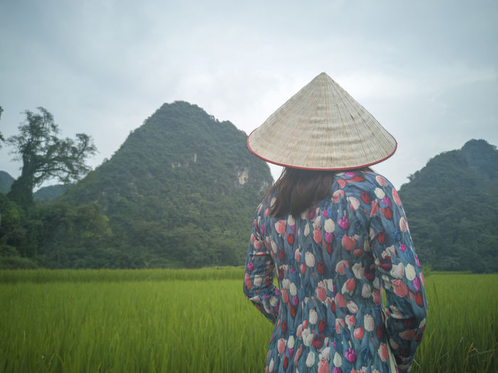 Rear view of woman with traditional clothes while standing on agricultural field