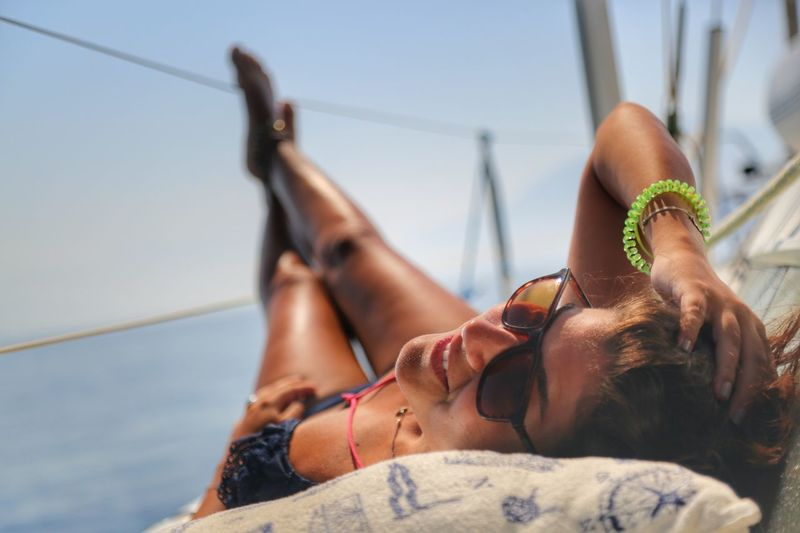 Midsection of beautiful woman sunbathing on deck