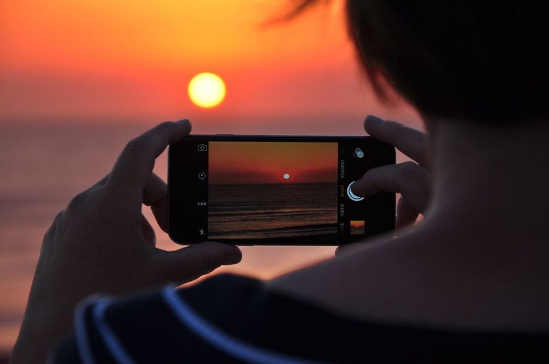 Person taking sunset shot on mobile